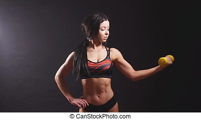 Portrait of young fitness woman shows biceps. Slow motion
