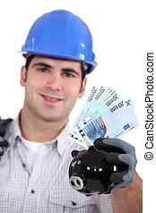 portrait of young foreman holding bills and piggy bank