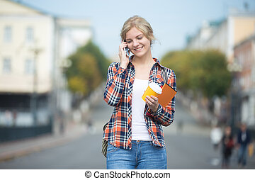Portrait of young girl against blurred street, talking on phone