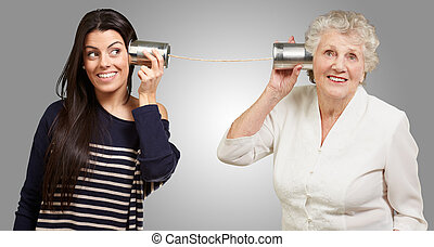 portrait of young girl and her grandmother hearing sounds using a metal tin can