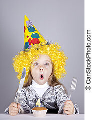 Portrait of young girl at birthday with cake.