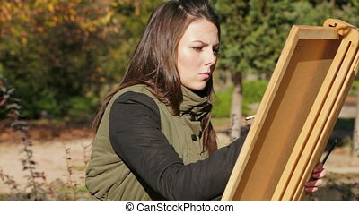 Portrait Of Young Girl Drawing Picture In Park