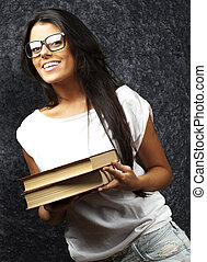 portrait of young girl holding books against a grunge wall