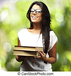 portrait of young girl holding books against a nature background