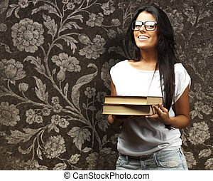 portrait of young girl holding books against a vintage wall