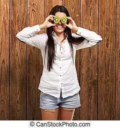 portrait of young girl holding kiwi slices in front of her eyes against a wooden wall