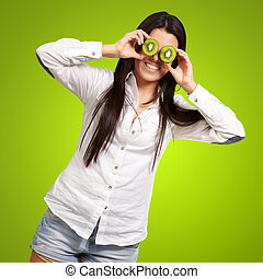 portrait of young girl holding kiwi slices in front of her eyes over green