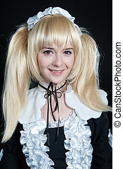 Portrait of young girl in anime lolita suit on black ...