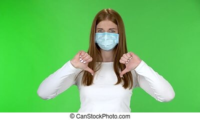 Portrait of young girl in medical protective face mask looking at camera and disgruntled shakes his head and shows fingers down on both hands. Redhead with long straight hair in a white blouse on a green screen in the studio. Health Protection Corona Virus Concept.