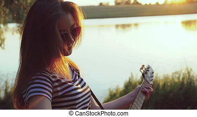 Portrait of young girl playing the guitar near the evening lake. 4k