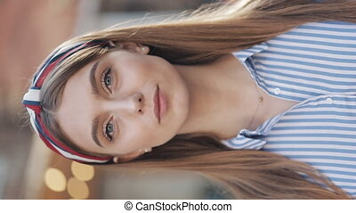 Portrait of Young Good Looking Girl with Brown Hair and Headband Wearing in Striped Dress Looking to Camera Standing at the City Street Vertical Video