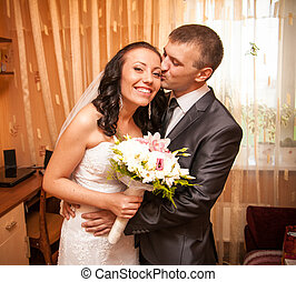 Portrait of young groom kissing bride in room