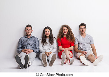 Portrait of young group of friends sitting on the floor in a studio.