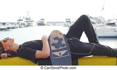 young guy lying on skateboard spending time at skatepark