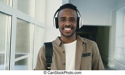 Portrait of young handsome afro student dancing while standing in wide white corridor of college wearing big headphones listening to music looking at camera and smiling