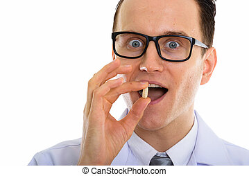 Portrait of young handsome man doctor with eyeglasses holding medicine pills