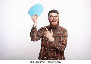 young handsome man with beard wearing glasses and pointing at speech bubble