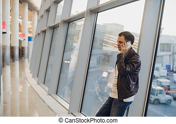 Portrait of young handsome person wearing casual style clothes standing near window in modern airport terminal. Traveler making call using smartphone.