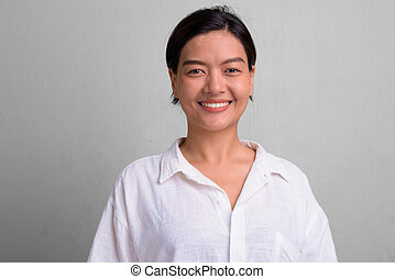 Studio shot of young beautiful Asian woman with hair tied against white background