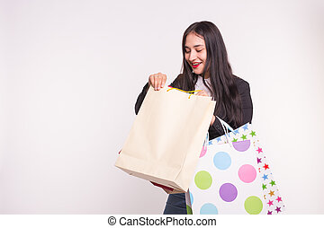 Portrait of young happy brunette woman with shopping bags on white background with copy space