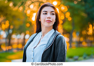 Portrait of young happy business woman in the city. Beautiful caucasian student girl in white sexy blouse standing in the autumn street.
