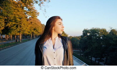 Portrait of young happy business woman walking alone the city. Beautiful caucasian student girl in white sexy blouse enjoying free time at autumn street. Slow motion