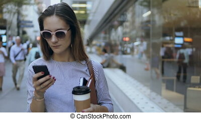 Portrait of young happy businesswoman standing with coffee cup near the office building and using the smartphone.