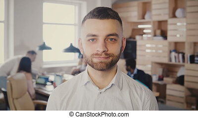 Portrait of young happy Caucasian businessman posing at busy...