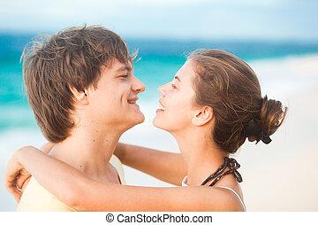 portrait of young happy couple having fun on tropical beach. honeymoon