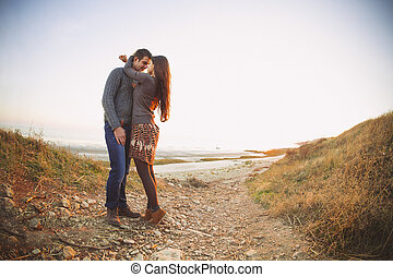 Portrait of young happy couple laughing in a cold day by the sea
