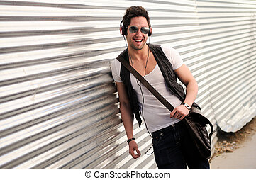 Portrait of young happy man smiling in urban background