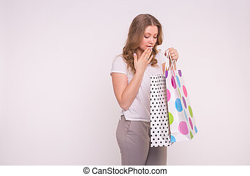 Portrait of young happy smiling woman with shopping bags on white background with copy space
