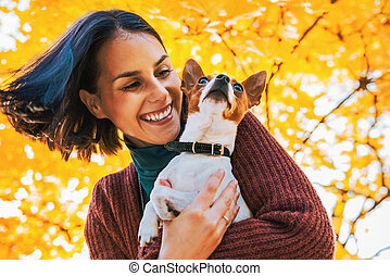 Portrait of young happy woman with little cute dog in park
