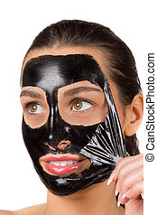 Portrait of young healthy woman with black peel face mask.