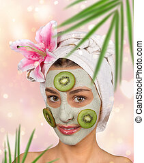 Portrait of young healthy woman with face clay mask.