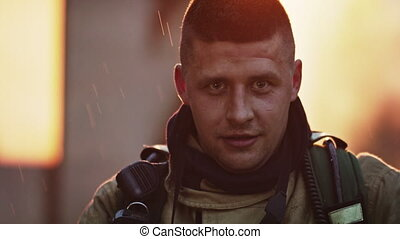 Portrait of young heroic fireman in front of burning house