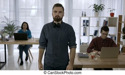 Portrait of young hipster with beard at workplace - Portrait...