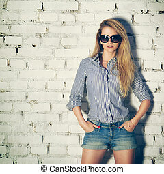 Portrait of Young Hipster Woman at the Brick Wall