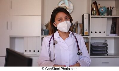 Portrait of young hispanic female doctor in face mask making welcome gesture welcoming patient to clinic