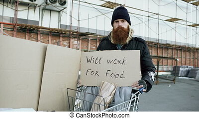 Portrait of young homeless man with cardboard looking at...