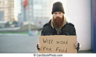 Portrait of young homeless man with cardboard looking at camera and wants to work for food looking at camera at street