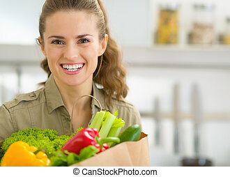 Portrait of young housewife in kitchen