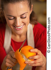 Portrait of young housewife removing orange peel