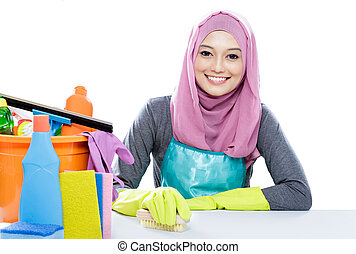 young housewife wearing hijab cleaning a table using brush