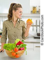 Portrait of young housewife with fresh vegetables in modern kitchen