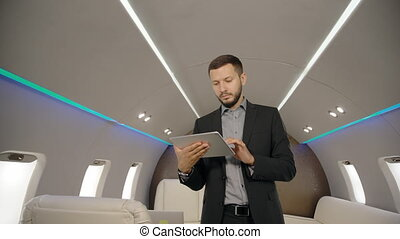 Portrait of young investor expert analyst PR-manager reading news on his tablet standing in private jet.