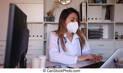 Portrait of young latina female doctor in face mask working on laptop in clinic office