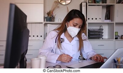 Young hispanic woman doctor assistant in protective face mask working in medical office using laptop computer