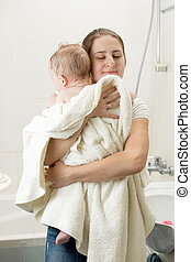 Portrait of young loving caring mother huggging her baby after washing in bath