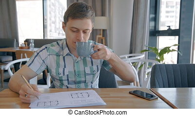 Portrait of young male architect working on blueprint, drinking coffee and having phone talk in cafe.